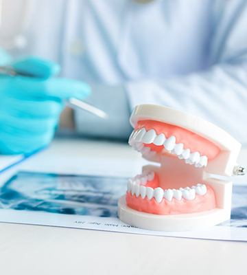 Dentist sitting at desk, answering questions about dentures in Colleyville