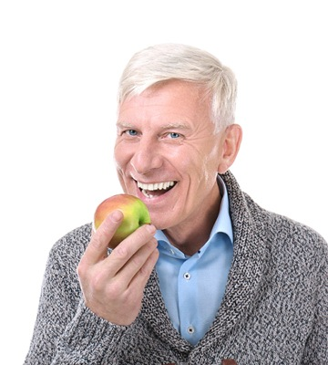 senior man with strong teeth eating an apple