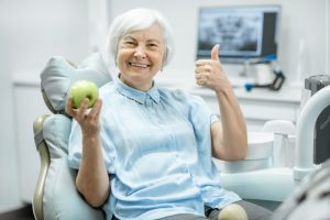 older woman smiling in dentist chair