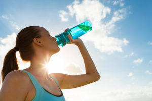 Woman drinking water after going on a run